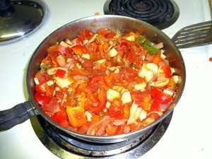a sauce pan with tomatoes, potatoes, red bell pepper, jalapeno, onion, and garlic in it